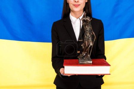 Photo pour Vue recadrée de l'avocat dans le procès noir retenant la figurine de Themis sur le livre sur le fond ukrainien de drapeau - image libre de droit