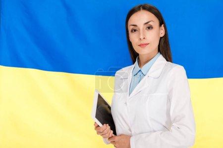Photo pour Docteur dans le manteau blanc retenant la tablette numérique sur le fond ukrainien de drapeau - image libre de droit