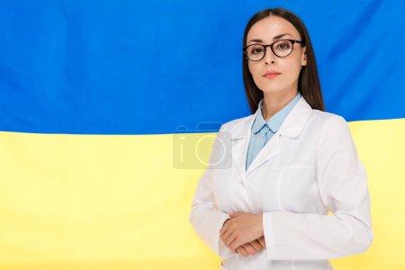 Photo pour Médecin confiant dans le manteau blanc sur le fond ukrainien de drapeau - image libre de droit