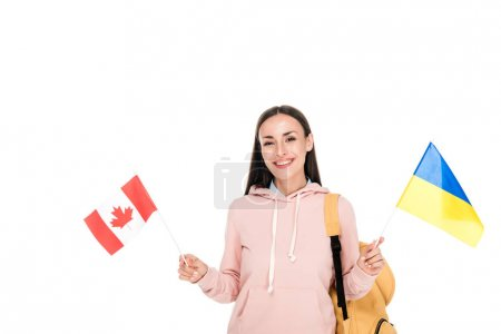 smiling student with backpack holding Ukrainian and Canadian flags isolated on white