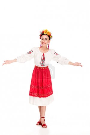 Photo for Full length view of happy brunette young woman in national Ukrainian costume doing welcome gesture isolated on white - Royalty Free Image