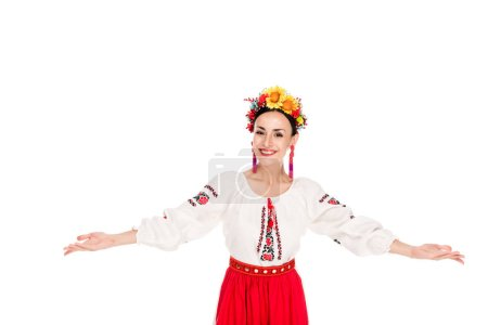 Photo for Happy brunette young woman in national Ukrainian costume doing welcome gesture isolated on white - Royalty Free Image