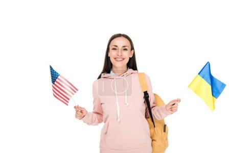 Photo pour Étudiant de sourire avec le sac à dos retenant les drapeaux ukrainiens et américains d'isolement sur le blanc - image libre de droit