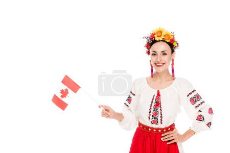 brunette young woman in national Ukrainian costume holding flag of Canada isolated on white
