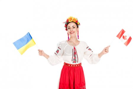Photo for Smiling brunette young woman in national Ukrainian costume holding flags of Ukraine and Canada isolated on white - Royalty Free Image