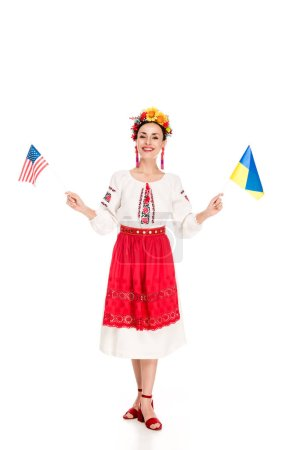 Photo for Happy brunette young woman in national Ukrainian costume holding American and Ukrainian flags isolated on white - Royalty Free Image