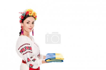 Photo pour Side view of brunette young woman in national Ukrainian costume holding flag isolated on white - image libre de droit