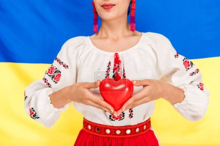 Photo for Partial view of young woman in national Ukrainian costume holding red heart with flag of Ukraine on background - Royalty Free Image