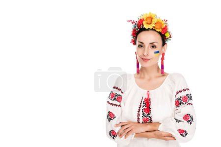 Photo for Brunette young woman in national Ukrainian embroidered shirt and floral wreath with crossed arms isolated on white - Royalty Free Image