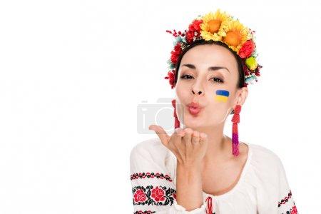Photo pour Jeune femme brune dans la chemise brodée ukrainienne nationale et le baiser de souffle de couronne florale d'isolement sur le blanc - image libre de droit