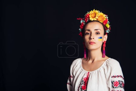 Photo for Brunette young woman in national Ukrainian costume and floral wreath looking at camera isolated on black - Royalty Free Image