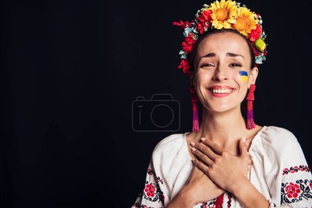 Photo for Happy brunette young woman in national Ukrainian costume isolated on black - Royalty Free Image