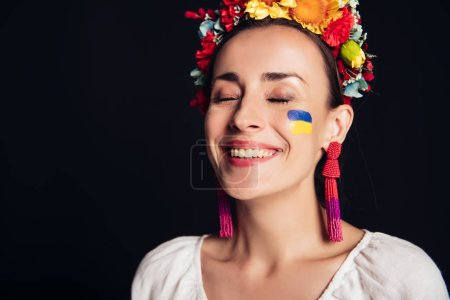 Photo for Happy brunette young woman in national Ukrainian costume with closed eyes isolated on black - Royalty Free Image