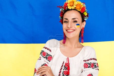 Photo pour Happy brunette young woman in national Ukrainian costume and floral wreath with flag of Ukraine on background - image libre de droit