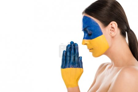 Photo for Side view of naked young woman with painted Ukrainian flag on skin praying with closed eyes isolated on white - Royalty Free Image
