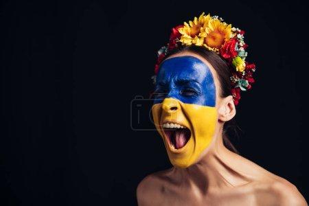 Photo pour Jeune femme nue dans la couronne florale avec le drapeau ukrainien peint sur la peau criant d'isolement sur le noir - image libre de droit