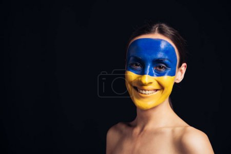 Photo for Naked young woman with painted Ukrainian flag on skin smiling isolated on black - Royalty Free Image