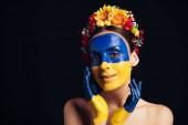 """Постер, картина, фотообои """"счастливая голая молодая женщина в цветочном венке с нарисованным украинским флагом на коже, кричащей изолированной на черном"""""""