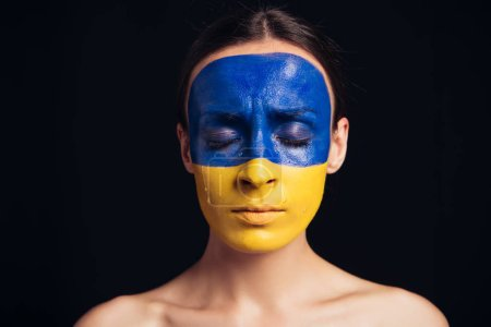 Photo pour Naked young woman with painted Ukrainian flag on skin and closed eyes isolated on black - image libre de droit