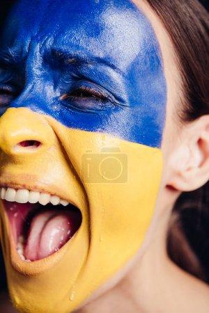 Photo pour Fermez-vous vers le haut de la vue de jeune femme avec le drapeau ukrainien peint sur la peau criant et pleurant isolé sur le noir - image libre de droit