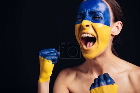 Photo for Naked young woman with painted Ukrainian flag on skin screaming isolated on black - Royalty Free Image