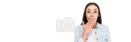 Photo pour Femme excitée de brunette couvrant la bouche avec la main d'isolement sur le blanc, projectile panoramique - image libre de droit