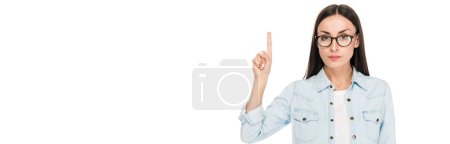 brunette girl in glasses in denim jacket pointing with finger upwards isolated on white, panoramic shot