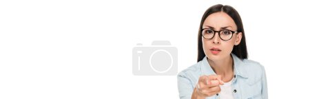 Photo for Angry brunette girl in glasses in denim jacket pointing with finger at camera isolated on white, panoramic shot - Royalty Free Image