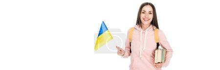 Photo pour Étudiant de sourire avec le sac à dos retenant le drapeau ukrainien et les livres d'isolement sur le blanc, projectile panoramique - image libre de droit