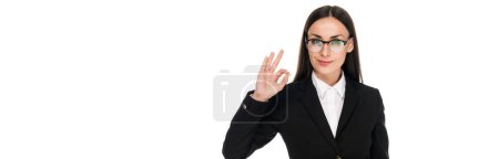 Photo for Smiling businesswoman in black suit showing ok sign isolated on white, panoramic shot - Royalty Free Image