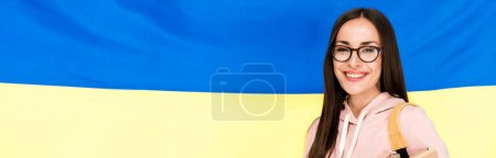 smiling brunette young woman with backpack on Ukrainian flag background, panoramic shot