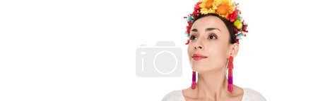 Photo for Brunette young woman in national Ukrainian embroidered shirt and floral wreath looking away isolated on white, panoramic shot - Royalty Free Image