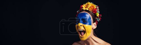 Photo pour Naked young woman in floral wreath with painted Ukrainian flag on skin screaming isolated on black, panoramic shot - image libre de droit