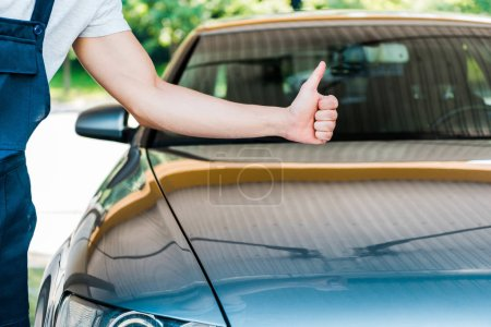 Photo for Cropped view of car washer showing thumb up near grey car - Royalty Free Image