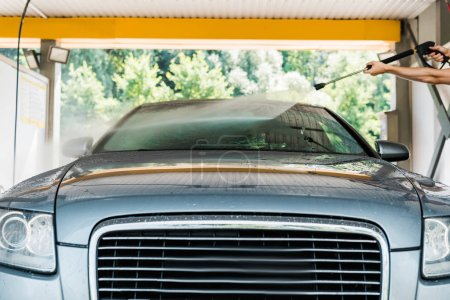 Photo for Cropped view of cleaner standing and washing grey automobile outside - Royalty Free Image