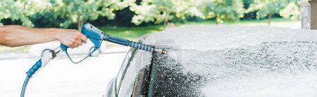 Photo for Panoramic shot of man holding pressure washer with foam near car - Royalty Free Image