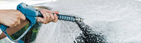 Photo for Panoramic shot of car cleaner holding pressure washer with foam near car - Royalty Free Image