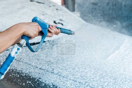 Photo for Selective focus of car cleaner holding pressure washer with foam near car - Royalty Free Image