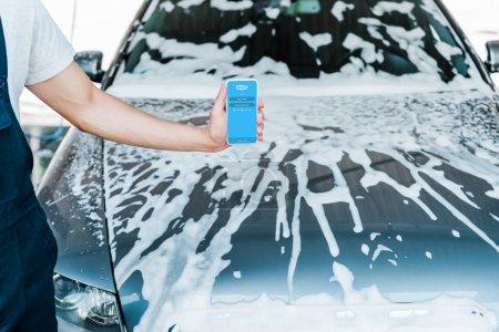 Photo pour Kiev, Ukraine - 20 juin 2019: vue recadrée de l'homme tenant smartphone avec l'application skype sur l'écran près de la voiture avec de la mousse - image libre de droit