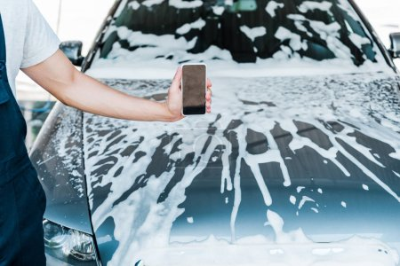 Photo for Cropped view of man holding smartphone with blank screen near car with foam - Royalty Free Image
