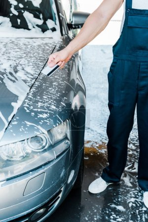 Photo for Cropped view of man holding credit card near car with foam - Royalty Free Image