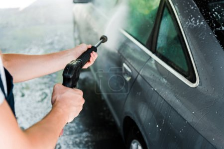 Photo for Cropped view of car cleaner holding pressure washer while standing near car - Royalty Free Image