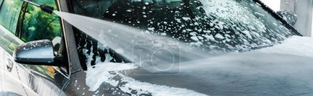Photo for Panoramic shot of pressure washer with water on grey modern car with foam - Royalty Free Image