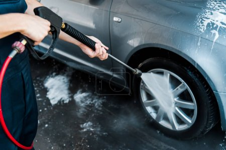 Photo for Selective focus of man holding pressure washer with water while standing near car - Royalty Free Image