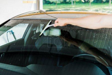 Photo pour Vue recadrée de laveuse de voiture retenant le squeegee tout en nettoyant la fenêtre de voiture - image libre de droit