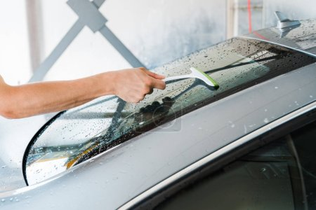 Photo for Cropped view of car washer holding squeegee and cleaning wet car window - Royalty Free Image