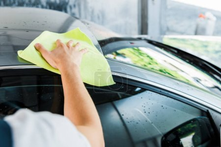 Photo for Selective focus of car washer holding green rag and cleaning car - Royalty Free Image