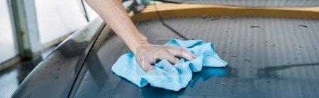 Photo pour Tir panoramique de l'homme nettoyant la voiture humide avec le chiffon bleu - image libre de droit