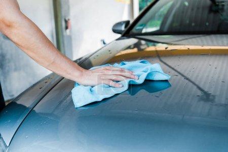 Photo pour Vue recadrée de l'homme nettoyant la voiture humide avec le chiffon bleu - image libre de droit