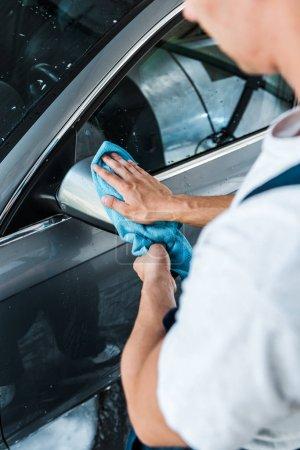 Photo pour Vue raccourcie de lave-voiture nettoyant miroir humide de voiture avec le chiffon bleu - image libre de droit